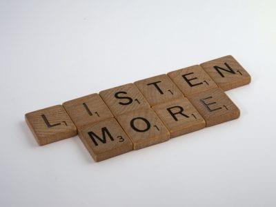 scrabble pieces spelling 'listen more'