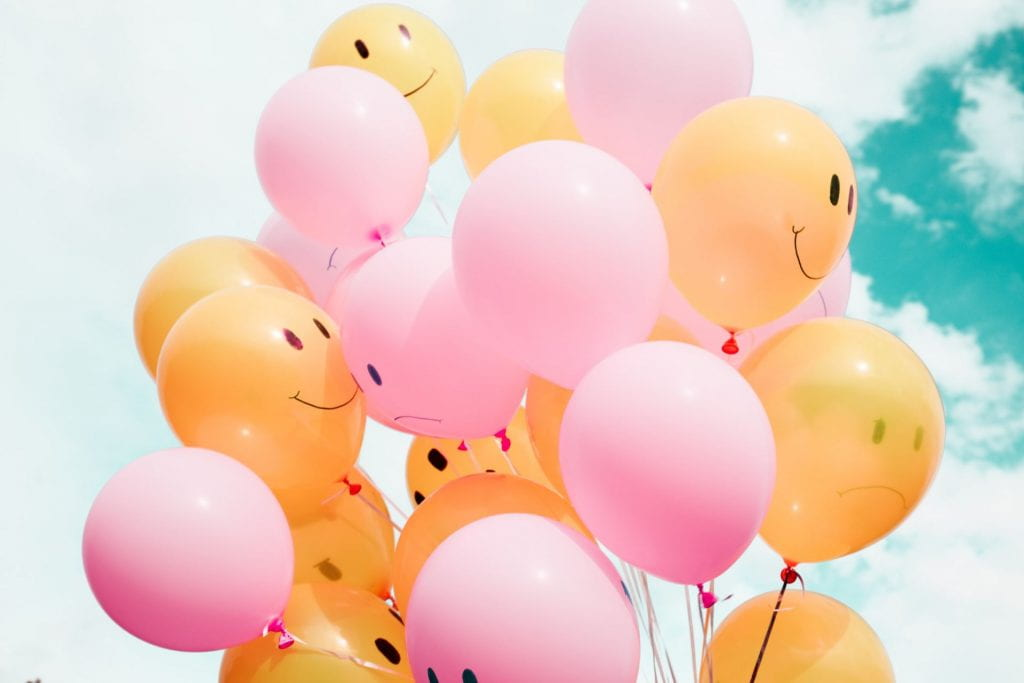 Orange and pink balloons with smiley faces on them. Some faces are sad, some are happy.