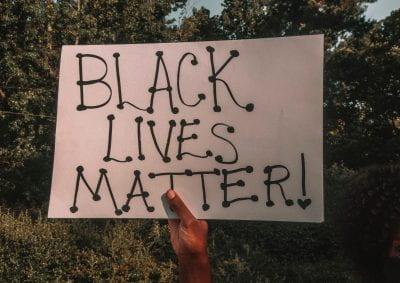 Hand holding sign saying' 'Black Lives Matter'