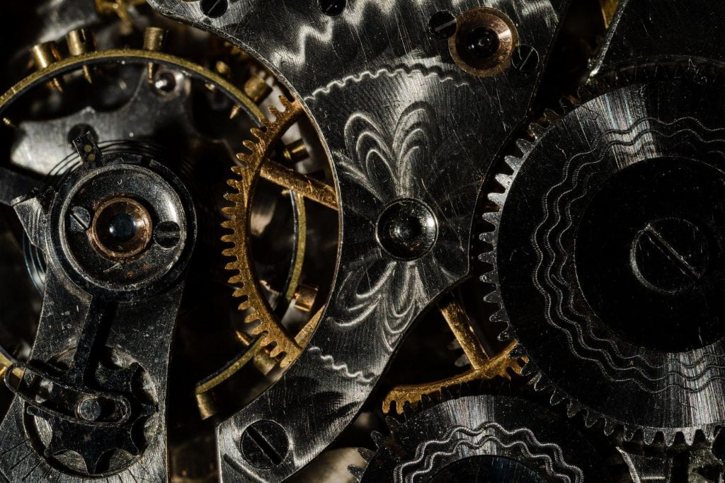 Many different cogs forming inside gears of a pocket watch.