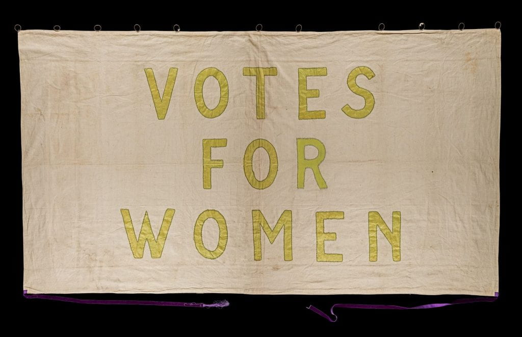 A suffragette banner with white background and green letters stating Votes For Women.