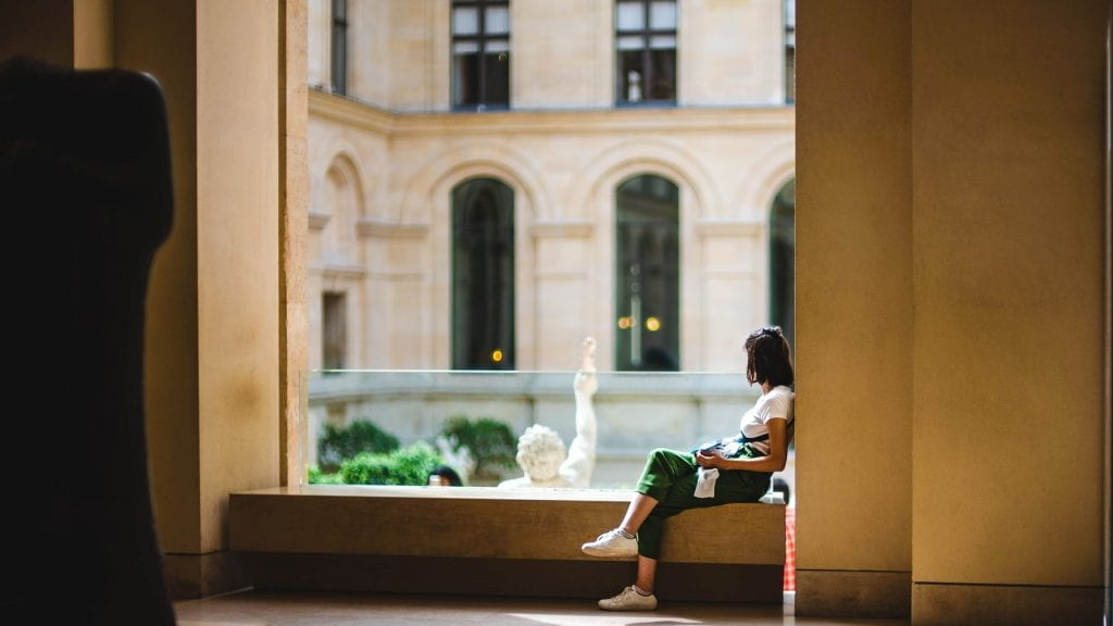 A young art student admiring the marble statues at the Museum de Louvre.