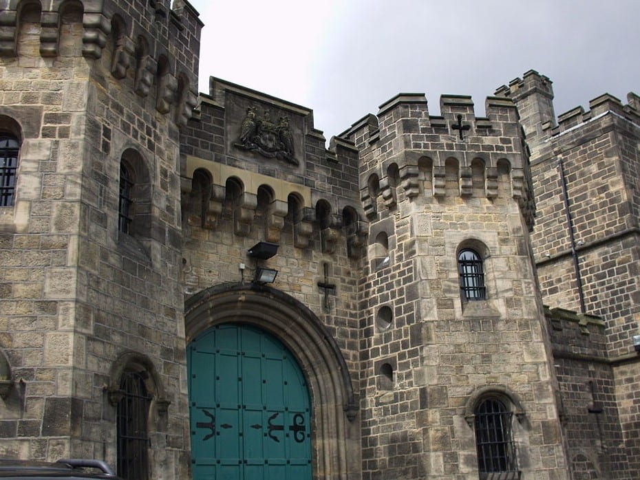 The old gate of the prison in Leeds. A monumental stone front with a medieval gate.