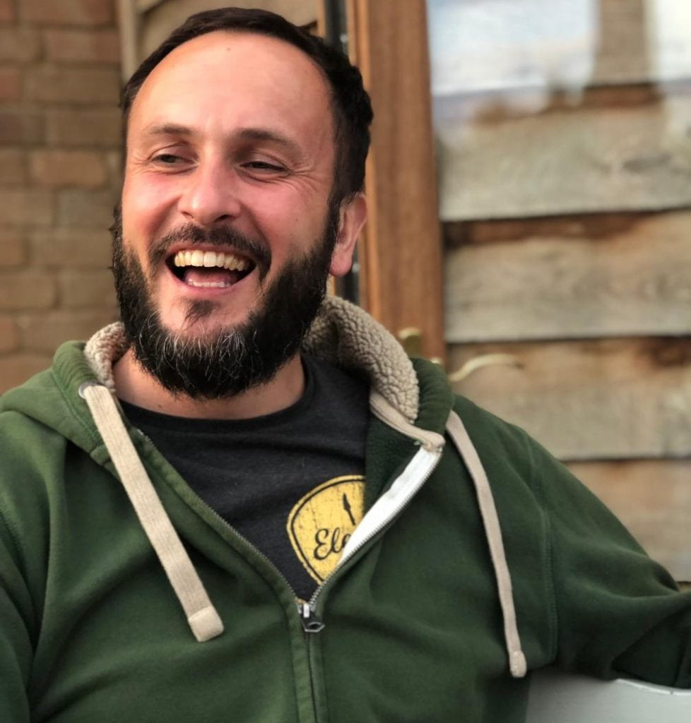Gary is captured in this photo in the middle of a hearty laugh. He is outside, wearing a green hoodie and has a dark beard.