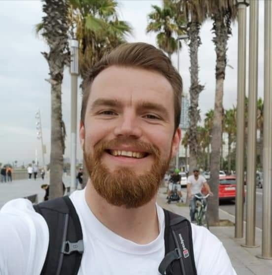 Jack is one of the co-authors of this blog. He is seen in this picture outside with palm trees int he background, wearing a white t-shirt.