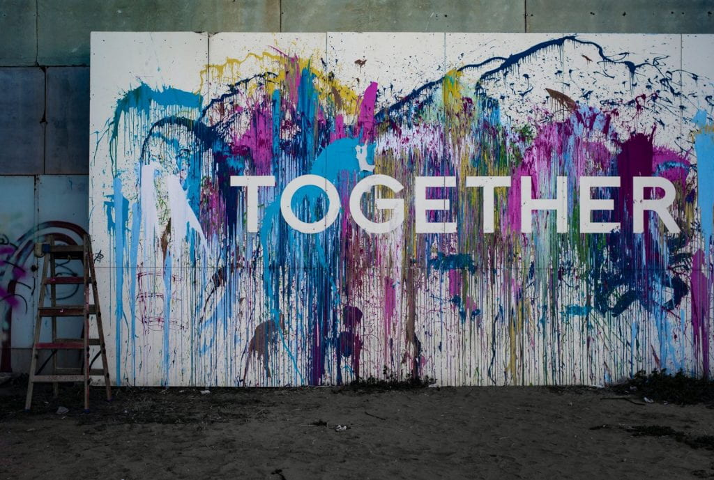 A white wall with multi colours splashed on it and the word 'TOGETHER' in white