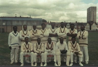 photograph of all-black and male cricket team. 8 of the players are standing at the back with their arms folded and there are 5 men sitting in front of them.