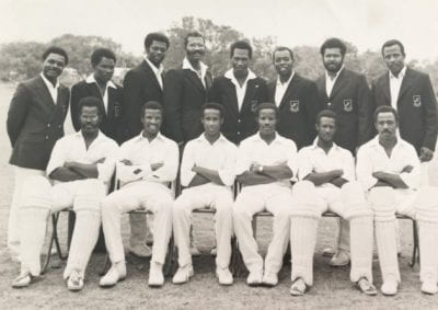 a black and white photograph. the image is of an all-black, male cricket team. There are 8 men standing at the back, each wearing a white shirt and dark blazor. In front of them there are 6 men sitting with their arms folded and each wearing a white cricket uniform and shin guards.