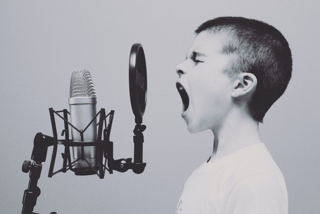 A young person screams into an old style microphone