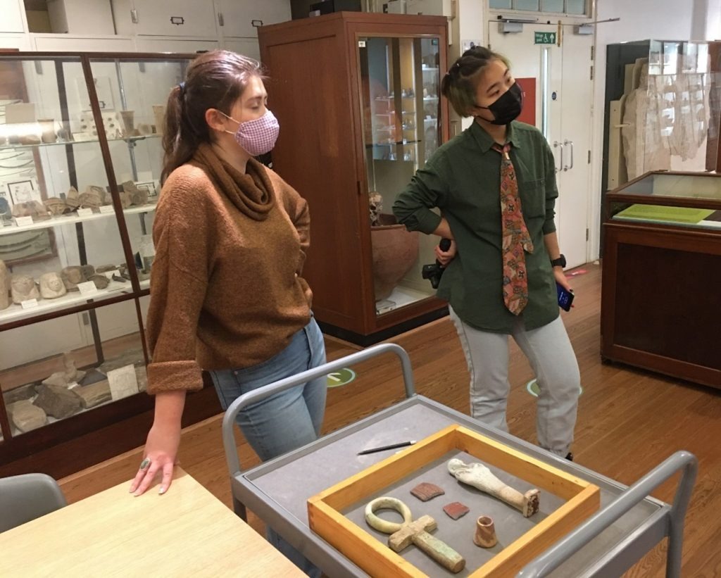 Two students stand in the Petrie Museum surrounded by artefacts with 3D printed objects carefully laid on a cat in front of them