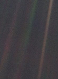 The Pale Blue Dot image, taken by the Voyager spacecraft on February 14th 1990 as a part of the family portrait. The Earth can be made out as a point of light in the leftmost chromatic aberration. Credit NASA