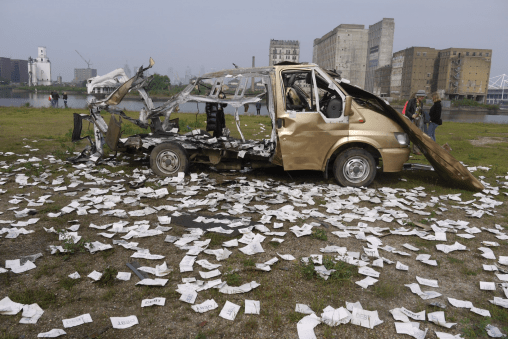 Shell of a van after a controlled explosion; pieces of paper marked 'debt' are scattered around
