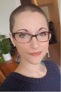 Dr Chloe Farahar photograph: close-up of a white woman with a shaved head, wearing purple glasses, looking into the camera