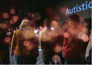 """Autie gang group picture: a group of audience members standing on a stage in a semi-circle, with a PowerPoint slide behind them which reads """"Autistic"""""""