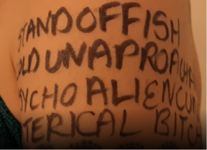 Annette Foster shoulder picture: close-up of a woman's bare shoulder where words have been written in Sharpie permanent marker. Words include: STANDOFFISH; COLD; UNAPPROACHABLE; PSYCHO; ALIEN; HYSTERICAL; B*TCH; C*NT