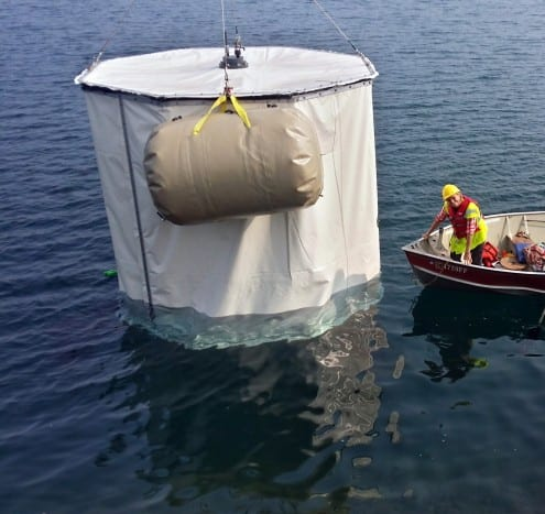 The CHIPS-M detector being lowered into the mine pit and filled with water. In the boat is UCL physicist Prof Jennifer Thomas. Photo courtesy Jerry Meier (University of Minnesota)