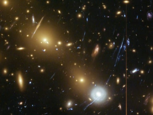 Gravitational lensing - the bending of the light from distant galaxies - can be used to estimate the mass of galaxy clusters (as the extent of the bending is directly proportional to the amount of mass present). Lensed light from distant galaxies is visible in this Hubble picture as streaks and arcs of light, most obviously the large diagonal streak of blue light in the right-hand side of the image. But it is fraught with difficulties. Photo credit: NASA, ESA, HST frontier fields (public domain)