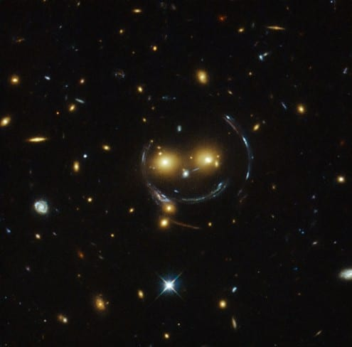 Gravitational lensing can dramatically distort the shapes of background galaxies, as can be seen in this Hubble image which shows galaxies distended into arcs around the cluster's centre of gravity. Credit: NASA/ESA (CC-BY)