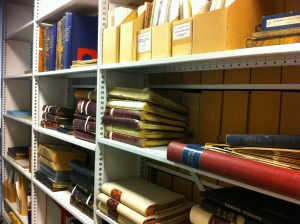 photograph of document boxes and volumes on shelves