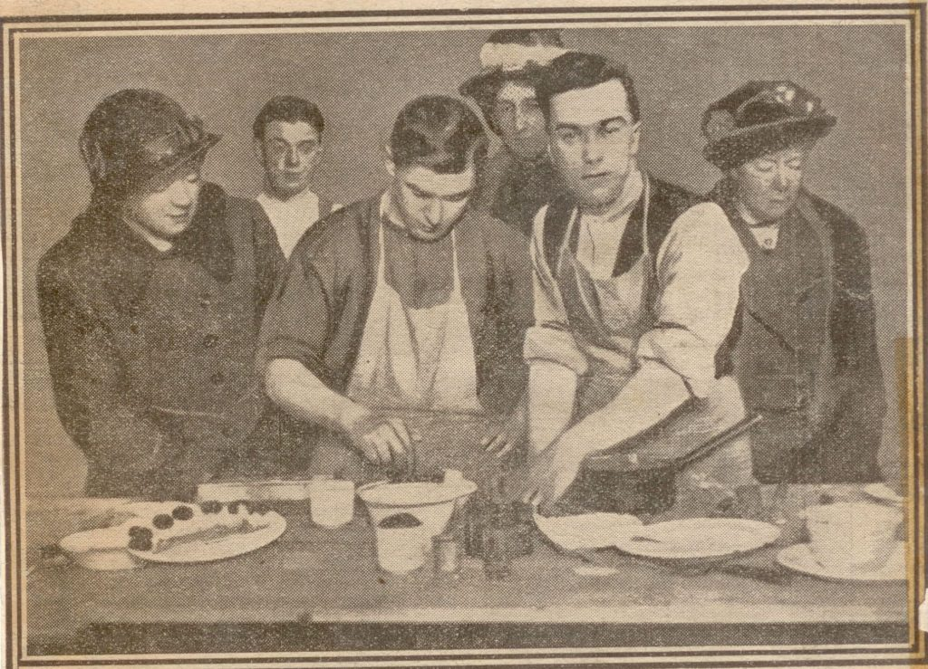 Image of a newspaper photograph showing 2 men preparing food whilst 3 ladies look on.