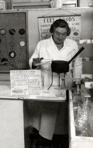 black and white photograph of woman pouring milk into a pan with a laboratory display around her.