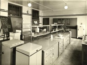 Black and white photograph of a teaching kitchen with electric cooker and fridge