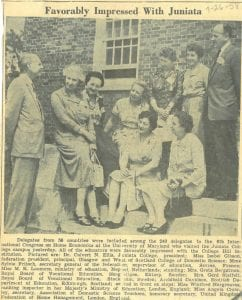 Newspaper cutting with photograph of delegates from the conference sitting outside on the College steps