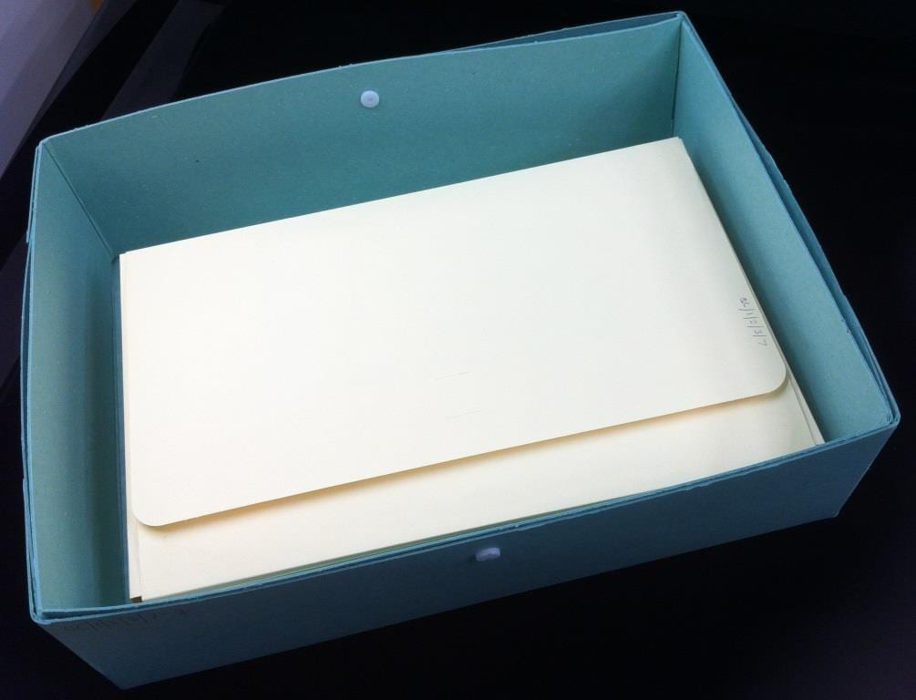 green box containing yellow folders with reference code written in pencil at top