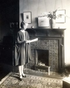 Black and white photograph of Dorothy Melvin standing at a fireplace reading a paper document