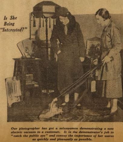 Newspaper cutting with photograph of a woman demonstrating an electric vacuum cleaner to a customer