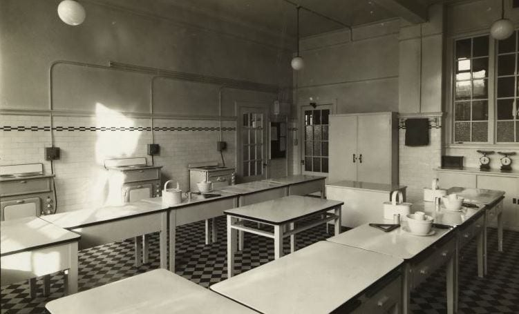Black and white photograph of a teaching kitchen with 3 electric cookers along the back wall