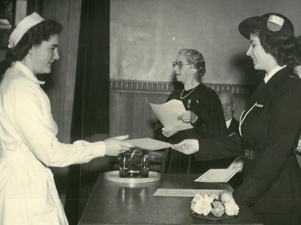 Black and white photograph of Princess Elizabeth handing a diploma to a student, with Dorothy Melvin in the background reading out names from a sheet.