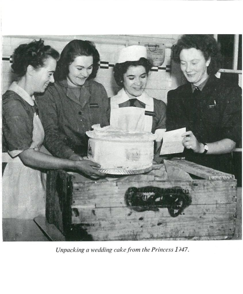 Black and white photograph of students with the tier of a wedding cake
