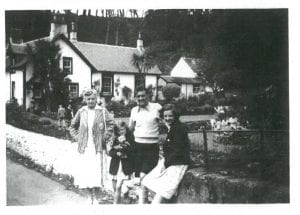 Photograph of man, woman and two children standing outside of a house