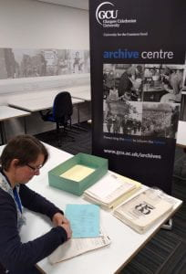 Colour photograph of Project Archivist working at a desk with bundles of papers with Archive Centre banner in the background.