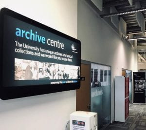 sign for GCU Archive Centre in foreground. Behind can see red lockers