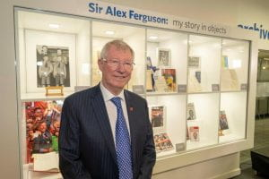 Sir Alex Ferguson standing at display of his objects at Sir Alex Ferguson Library