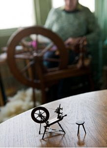Photograph of a model spinning wheel with a person spinning on a wheel in the background