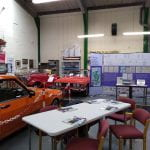 Photograph showing exhibition banners and table next to vintage cars