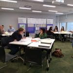 Photograph of a workshop session with people working round tables and exhibition banners in the background