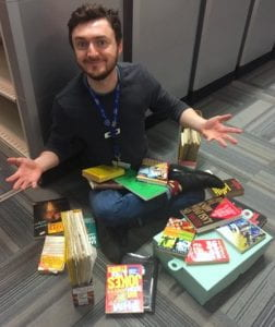 White man smiling at camera, seated. Books and magazines scattered around him