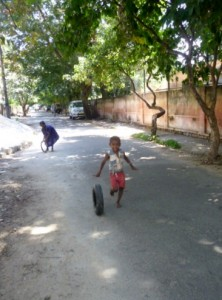An old tyre provides a toy for the amusement of a child on the streets in Bangalore city