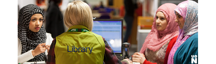 Students seeking help from a Library Customer Services Assistant