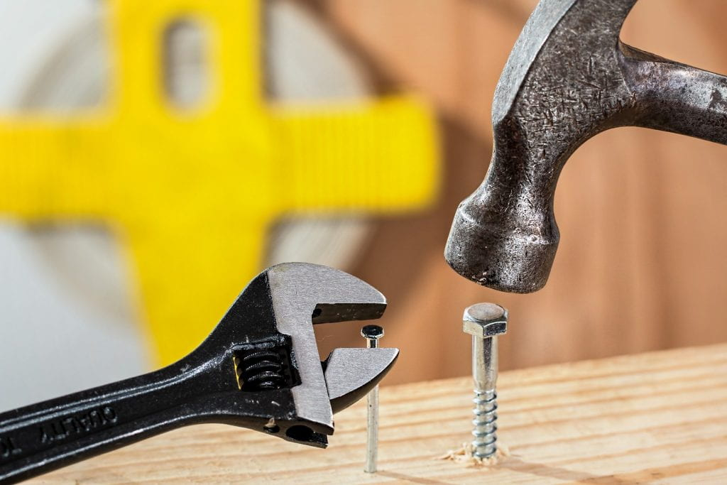 hammer banging in a bolt while a spanner tackles a nail