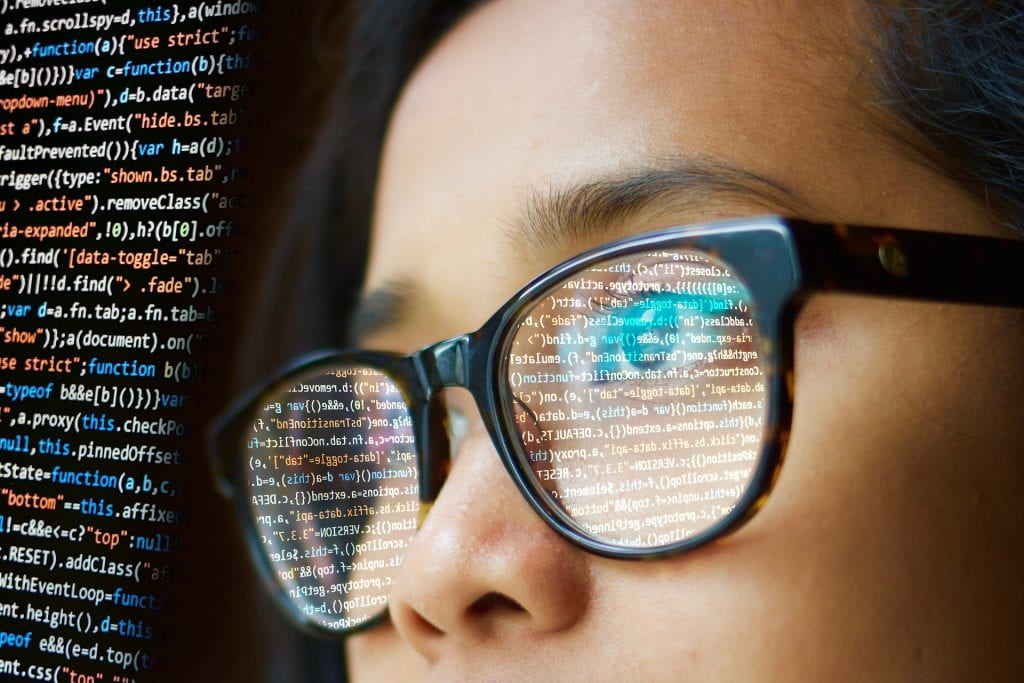 woman in glasses looking at screen full of computer code