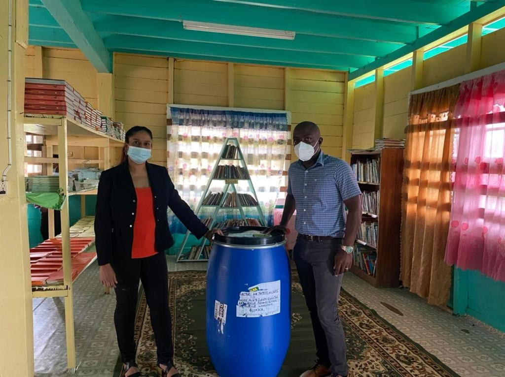 Mr Andries (my cousin) standing next to the barrel and the headmistress Mrs Dudnath-Ramotar