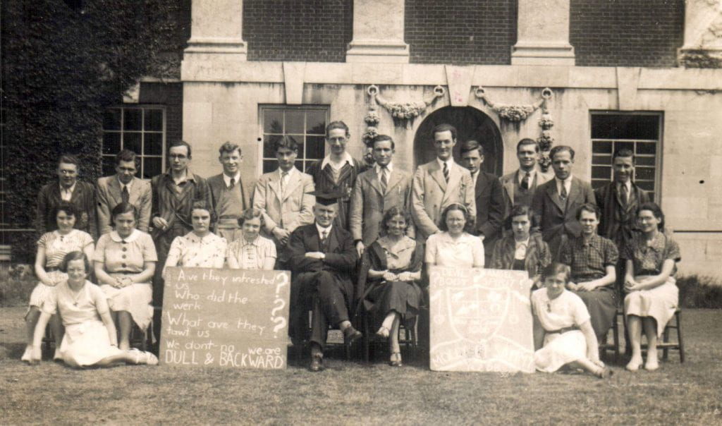 Advanced History group in front of the Blomfield building in 1938. Two women students in the front row playfully mock their supposed 'Advanced' status by chalking on a blackboard the deliberately misspelt 'Are they intrested in us? Who did the werk? What ave they tawt us? We don't know. We are DULL & BACKWARD'