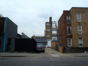 Photograph of the entrance to 79-89 Lots Road, Chelsea which is situated behind a block of flats.