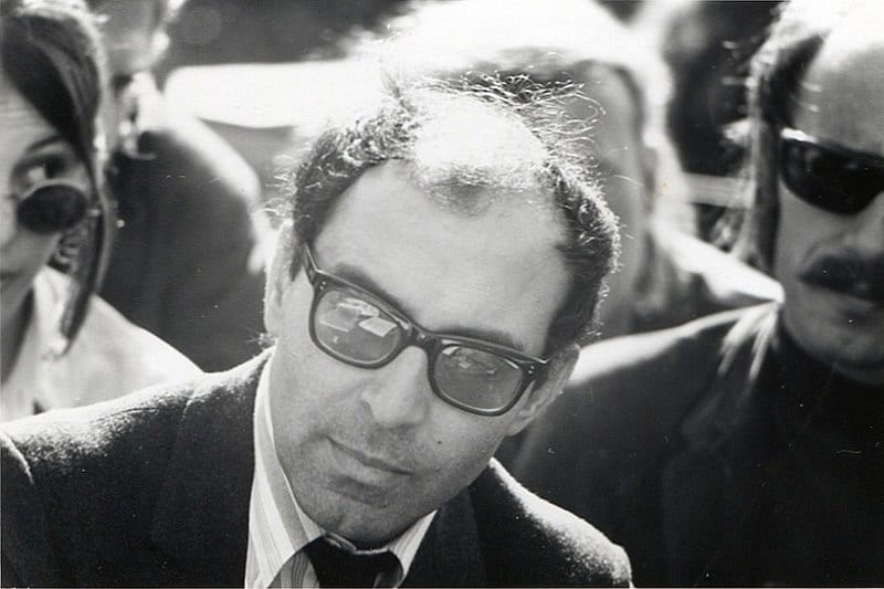 Black and white photographic portrait of Jean-Luc Godard wearing dark glasses at the University of Berkeley in California in 1968.