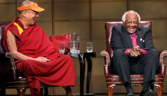 Colour photograph landscape of The 14th Dalai Lama and Archbishop Desmond Tutu, both Nobel Peace Prize laureates, in Vancouver, British Columbia, in 2004. Both seated and laughing at the same time.